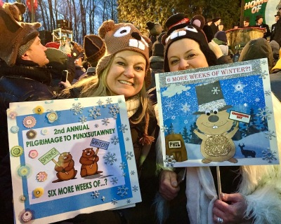 two women with groundhog hats holding homemade signs for Groundhog Day