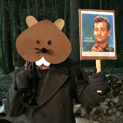man with groundhog mask and Bill Murray hand sign