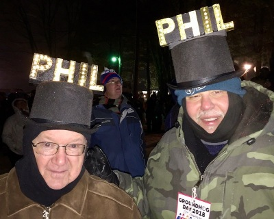 "two men wearing novelty top hats with light-up ""PHIL"" letters for Groundhog Day"