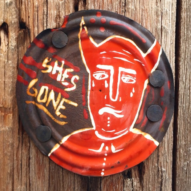 "tin can lid painted with sad devil and the words ""She's gone"", Pittsburgh, PA"