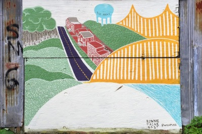 garage door covered with plywood painted with colorful bridge and hills, Pittsburgh, PA