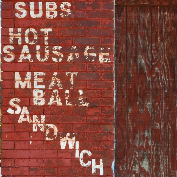 """brick wall of former hoagie shop painted with """"Subs,"""" """"Hot Sausage,"""" Meat Ball,"""" """"Sandwich,"""" Johnstown, PA"""
