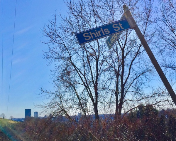 bent street sign for the intersection of Lappe Lane and Shirls Street with downtown Pittsburgh in the distance