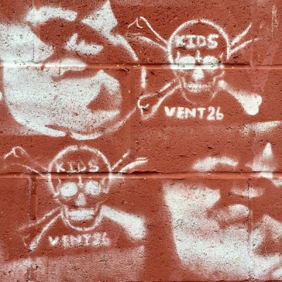 graffiti stencils of skull and crossbones and pig heads on cinderblock wall, Pittsburgh, PA