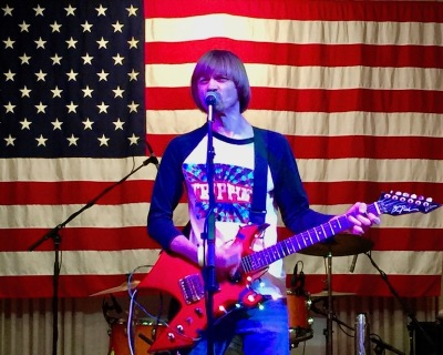 musician Weird Paul performing in front of an American flag, Pittsburgh, PA
