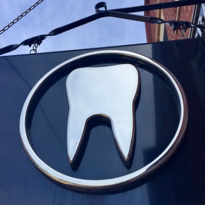 hanging sign with silver tooth in circle advertising dentist's office, Ambridge, PA