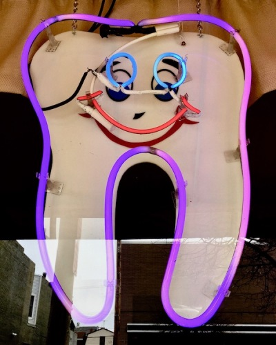 neon sign of large tooth with smiley face advertising dentist, Ambridge, PA