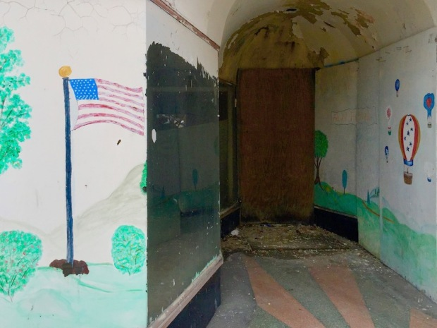 abandoned storefront with American flag painted on glass, Ambridge, PA