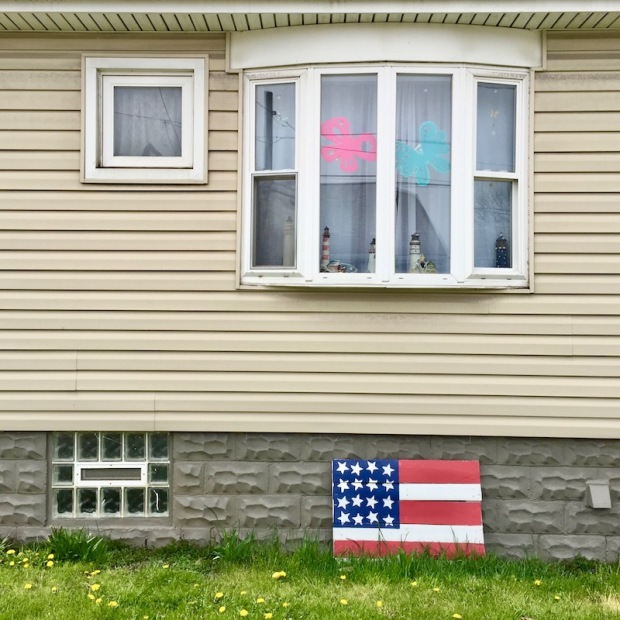 homemade American flag decoration leaning against house foundation, Neville Island, PA