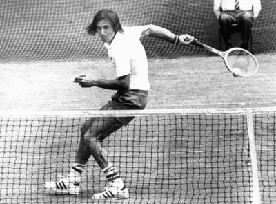 tennis player Ille Nastase hitting a ball behind his back