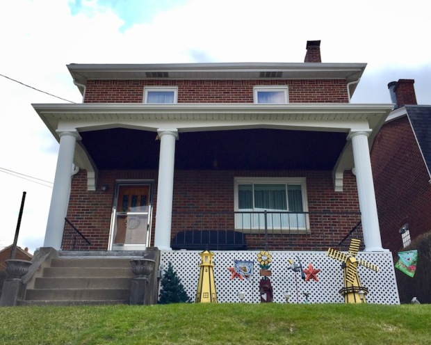decorative model lighthouses painted black-and-gold in front yard of house in Whitaker, PA