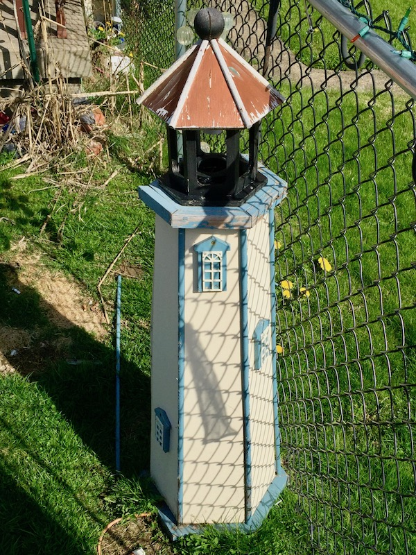 decorative lawn lighthouse against chain link fence, Donora, PA