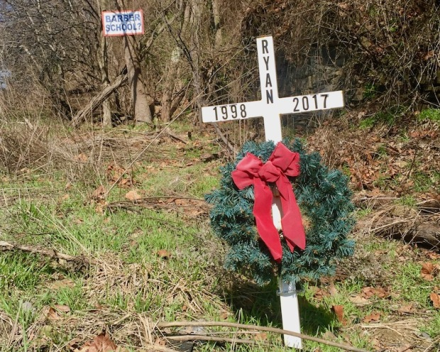 "roadside cross and wreath with lettering ""Ryan 1998-2017"""