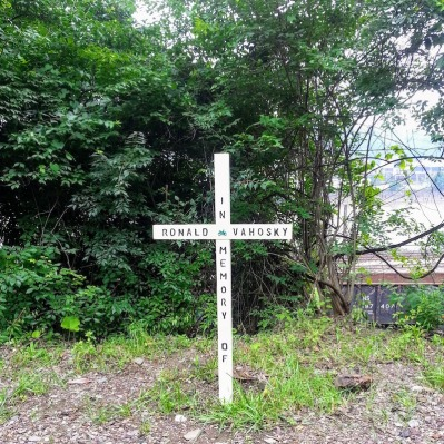 wooden memorial cross by bicycle trail