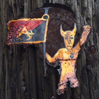 metal can lid painted with devil holding anarchy flag nailed to utility pole, Pittsburgh, PA