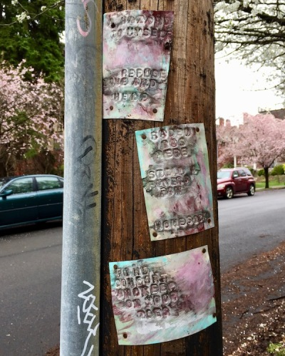 metal sheets stamped with words and painted, nailed to utility pole in Pittsburgh, PA