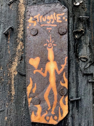 small painting of devil with heart on tin can nailed to utility pole, Pittsburgh, PA