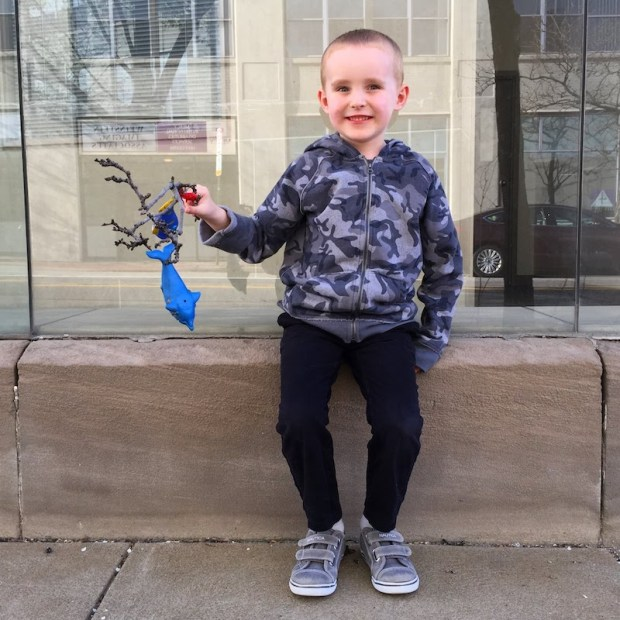 boy with tree twig and strand of toy fish