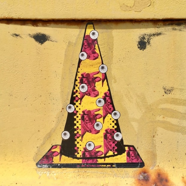 wheatpaste image of Andy Warhol wallpaper on traffic cone with eyeballs
