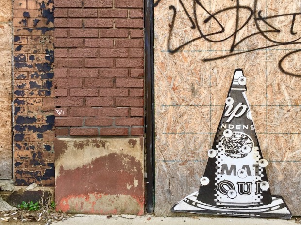 wheatpaste image of Campbell's Soup can on traffic cone with eyeballs