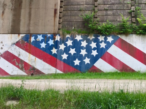 mural of American flag on retaining wall along bicycle trail