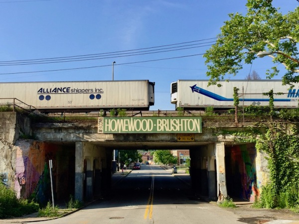 neighborhood welcome sign for Homewood-Brushton, Pittsburgh on train track overpass