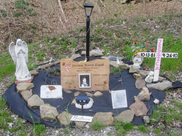 roadside memorial including painted cross, angel statue, inscribed stone, and solar garden light