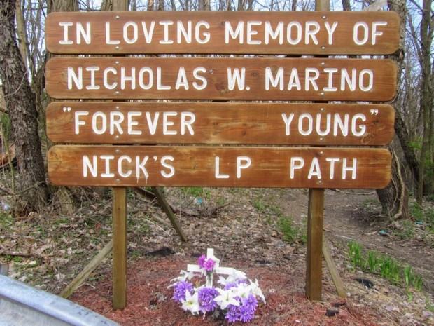 roadside memorial made from inscribed wooden planks