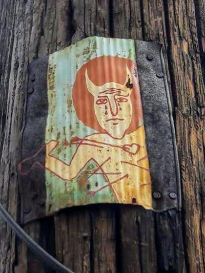 painting of devil with arrows piercing his chest, nailed to utility pole, Pittsburgh, PA