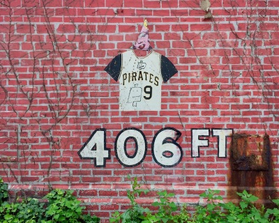 wheatpaste traffic cone with eyeballs on wall with Pirates baseball mural, Pittsburgh, PA