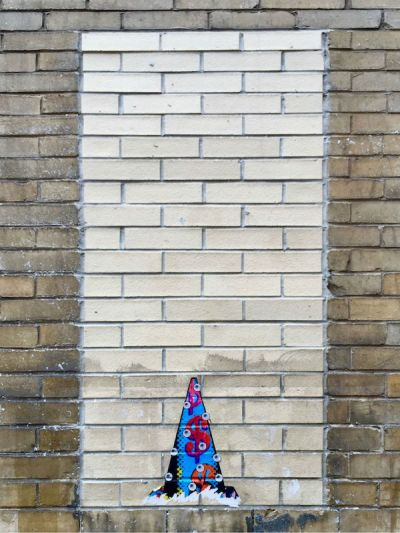 wheatpaste image of traffic cone with eyeballs on brick wall