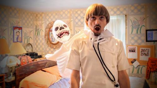 video still of Weird Paul dressed as a doctor with inflatable skeleton choking him