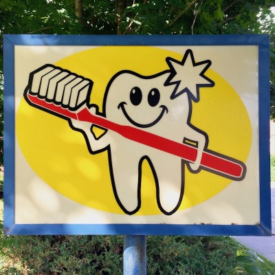 dental office sign with anthropomorphized tooth holding giant toothbrush, Clairton, PA