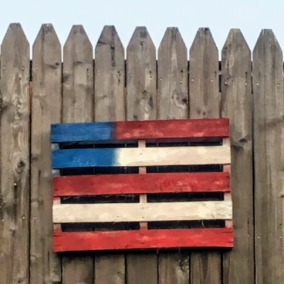 shipping pallet painted like American flag hanging on wooden fence