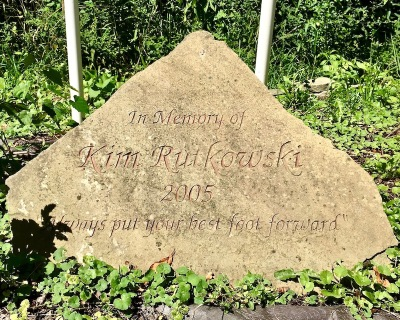 "engraved stone with the text ""In Memory of Kim Rutkowski, 2005, 'Always put your best foot forward'"""