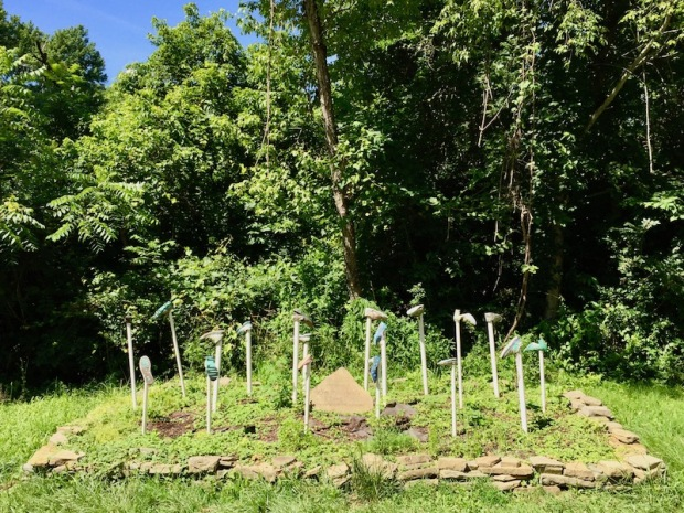 memorial with shoes nailed to PVC pipe planted in the ground