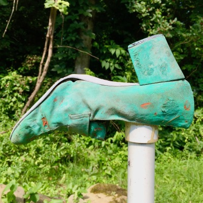 green ladies' shoe attached to PVC pipe