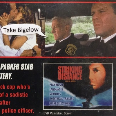 "detail of ""Striking Distance"" DVD case with ""Take Bigelow"" word balloon taped onto outside"