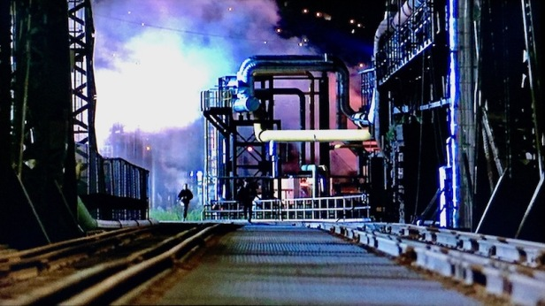 "scene from ""Striking Distance"" as two characters race on foot at factory"