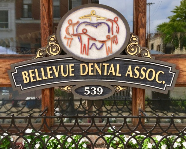 ornate sign for Bellevue Dental Associates with people forming ring around giant tooth