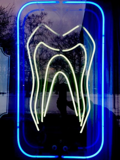 neon sign of large white tooth in blue frame, North Side Dental, Pittsburgh, PA