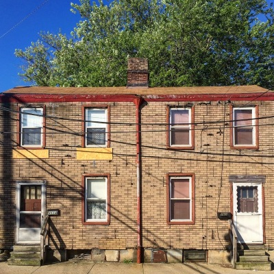 matched pair of row houses with fake brick siding, Pittsburgh, PA