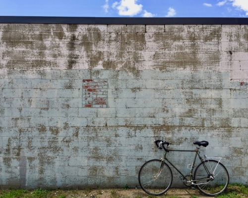 10-speed bicycle leans against a weathered cinderblock wall, Clairton, PA