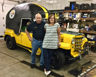 Ray and Kathi Kasunick in front of their 1950s era Willy's Jeepster painted in tribute to the Pittsburgh Steelers
