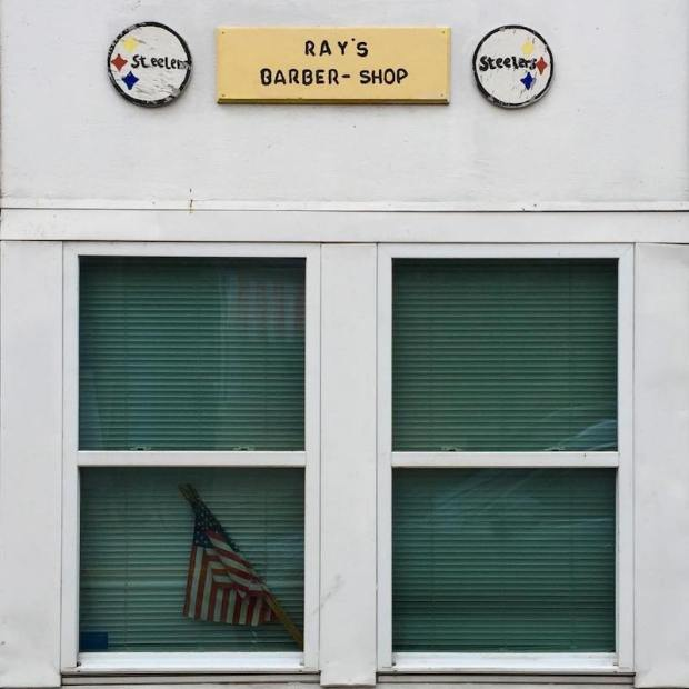 exterior of Ray's Barber Shop, Pittsburgh, with two homemade Steelers emblems