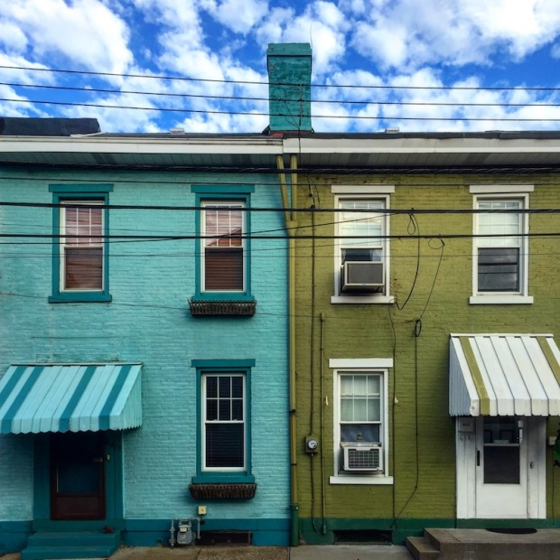 pair of brick row houses painted aqua blue and olive green, Pittsburgh, PA