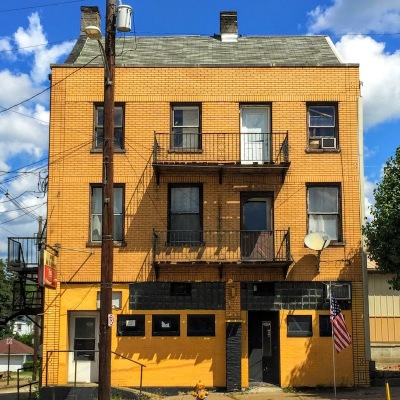 brick building with first floor bar exterior painted black and gold, Brownsville, PA