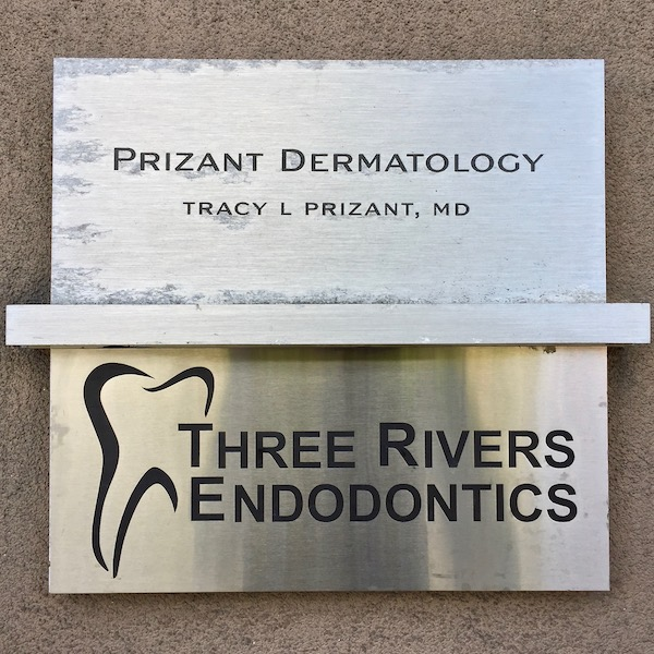 stainless steel sign for Three Rivers Endodontics with stylized tooth logo
