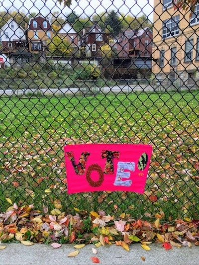 "handmade ""Vote!"" yard sign on chain link fence"