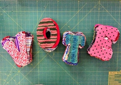 Fabric V-O-T-E letters on cloth sewing board